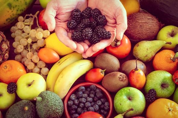 色とりどりの果物でいっぱいの木製のテーブルの上に新鮮なブラックベリーを持っている男の手