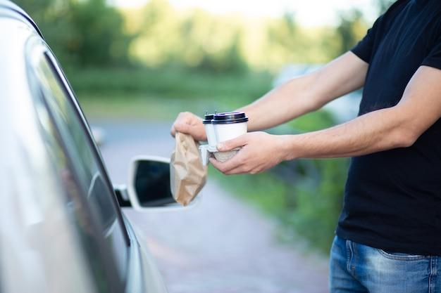 一杯のコーヒーとバッグを提供している男の手
