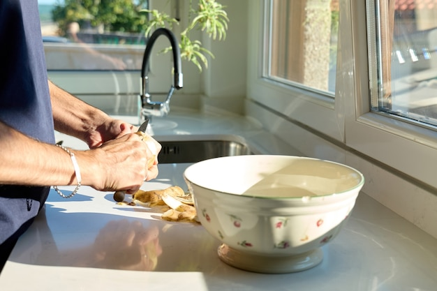 부엌에서 감자 껍질을 벗기는 남자의 손, 얼굴이 보이지 않는, 남자 요리 개념