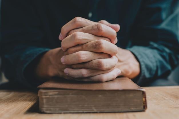성경 위에 기도하는 남자의 손은 일상 생활에서 믿음과 영성을 나타냅니다. 확대.