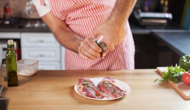木の板に赤身の肉をスライスするキッチンで肉と野菜を準備する男の手。