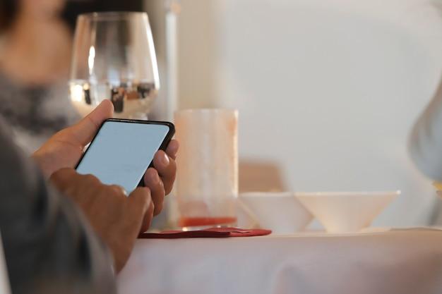 카메라 화면과 함께 휴대 전화를 사용하여 테이블에 앉아있는 남자의 손