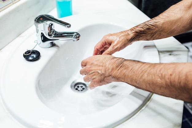 コロナウイルスに感染しないように、トイレで石鹸で洗う男の手。 covidのコンセプト。