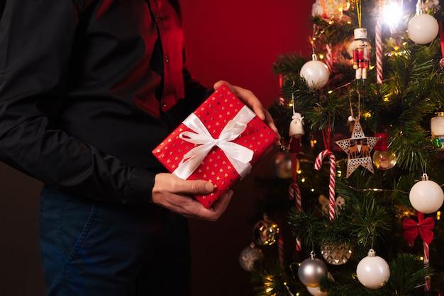 Руки человека с подарочной коробкой у елки для празднования нового года