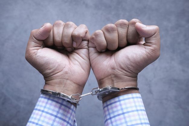 Руки человека с наручниками заделывают.