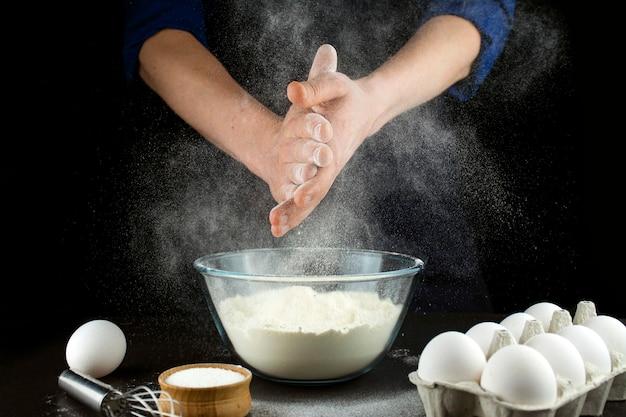 밀가루로 일하는 남자의 손. 요리 과정입니다. 어두운 배경입니다.
