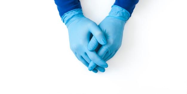 白いテーブルに青いラテックス手袋の人の手