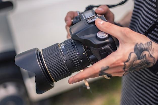 Руки фотографа, держащего зеркальный фотоаппарат