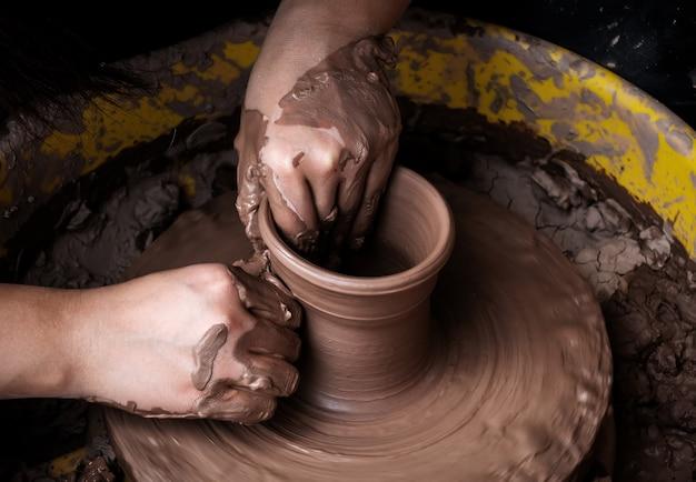 Руки гончара, создавая глиняную банку на круге