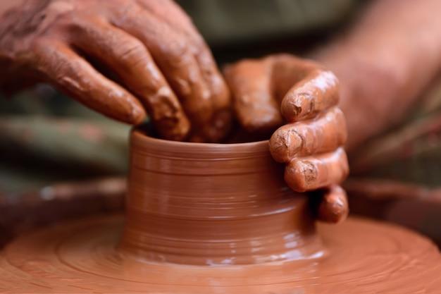 Руки гончара. гончар делает керамический горшок на гончарном круге