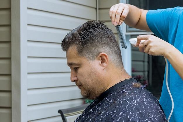 はさみと櫛でプロの理髪師の手は、男性のクライアントのために男性のヘアカットの髪をとかします
