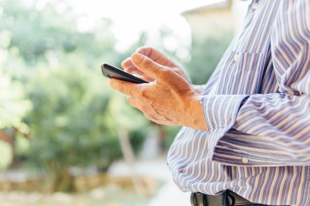 스마트 폰을 사용하는 시니어 남자의 손. 노인과 기술