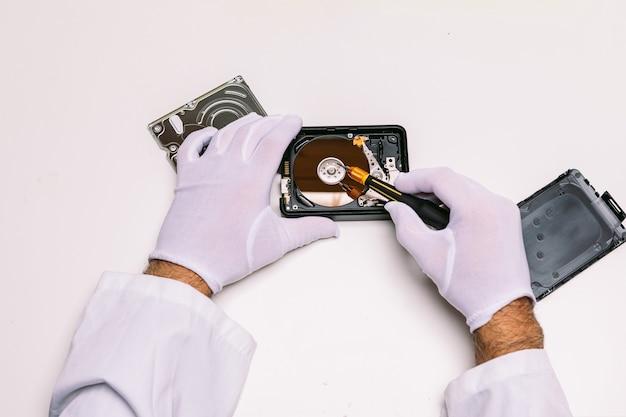 ハードドライブを修理する手袋をした技術者の手