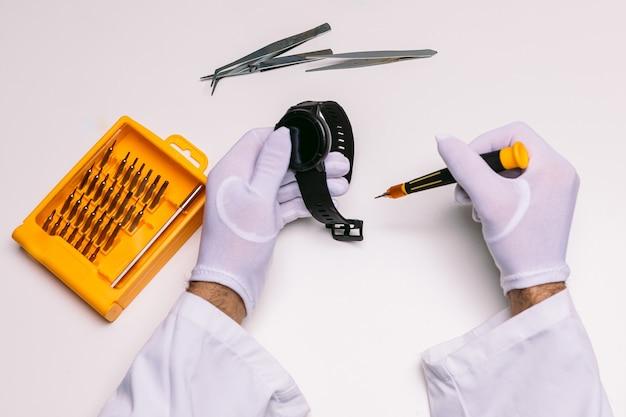 Руки техника в перчатках ремонтируют наручные часы smartwatch