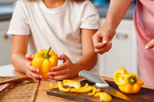 台所のテーブルでコショウを切る女性と彼女の子供の手