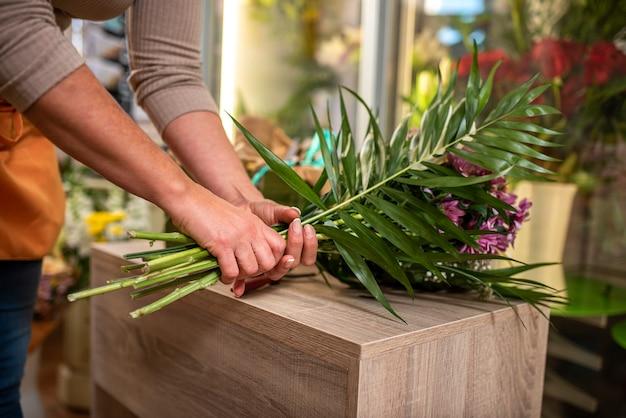Руки женщины, составляющей букет цветов на столе