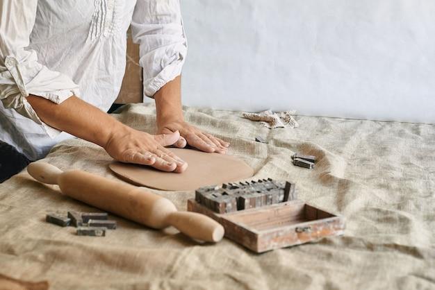 테이블 클로즈업에 점토 층을 반죽하는 여성 장인 도예가의 손