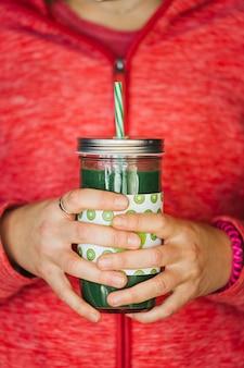 Руки женщины, держащей зеленую банку сока холодного отжима detox