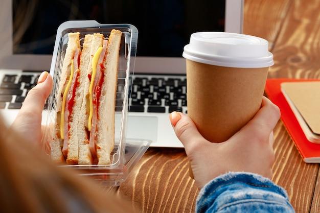 ノートパソコンで作業台の上にサンドイッチを保持している女性の手