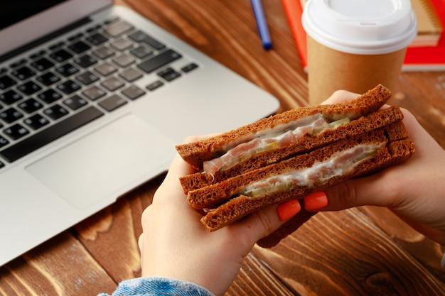 開いたラップトップで作業テーブルの上にサンドイッチを保持している女性の手