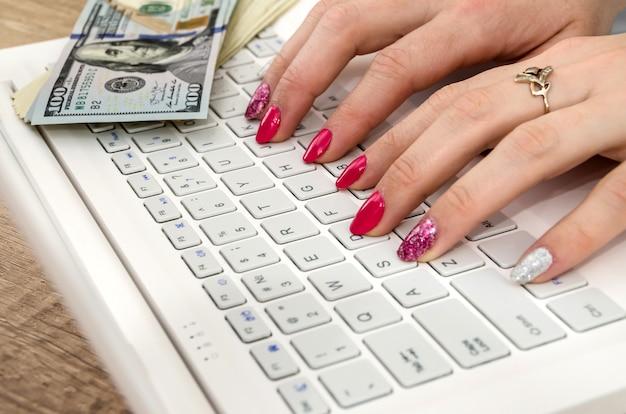 ノートパソコンのキーボードの女性の手