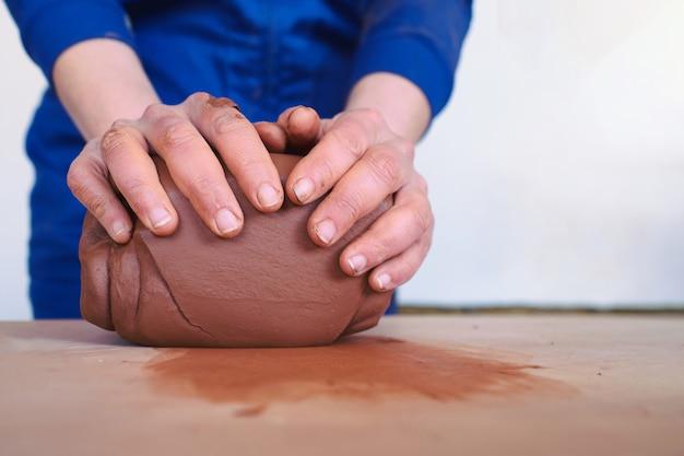 粘土を成形する女性の陶芸家の手