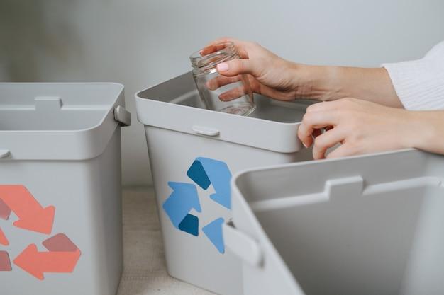 Руки женщины, сортирующей мусор между небольшими мусорными баками дома. на них нанесены стрелки разного цвета. держит стеклянную банку.