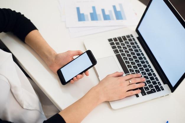 電話とラップトップを使用している女性の手