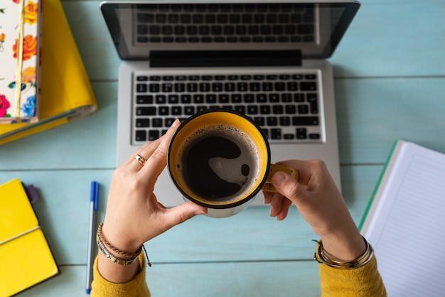 一杯のコーヒーを持った女性の手が彼女のラップトップで働いた。在宅勤務のコンセプト。