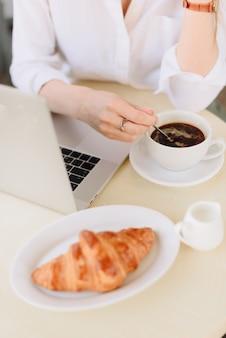夏の屋外カフェでコーヒーとノートパソコンを持つ女性の手