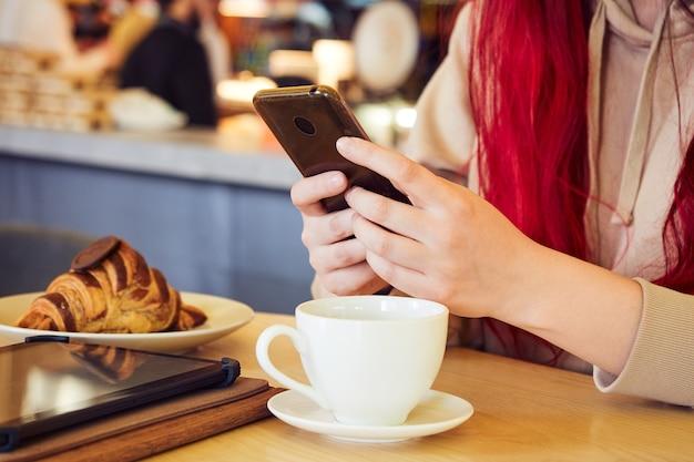 赤い髪の女性の手がクロワッサンとコーヒーを飲みながらレストランに座っているときに電話でメッセージを入力しています