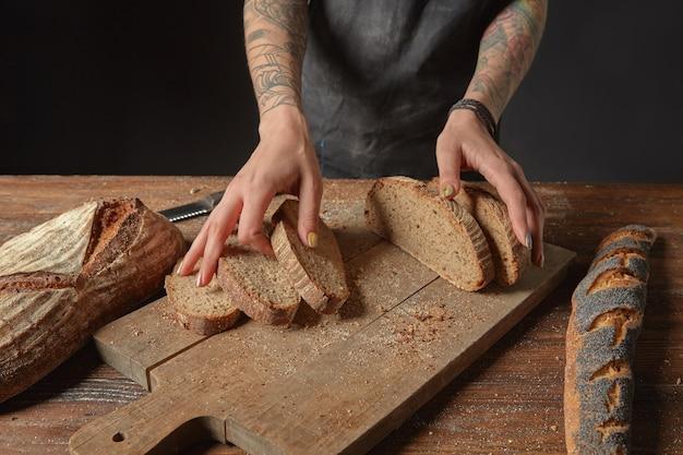 문신을 한 여자의 손에 호밀 빵 조각을 들고 밀가루로 굽기