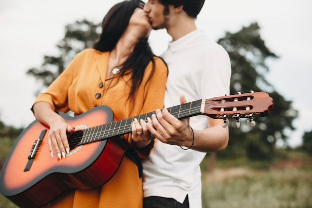 Руки молодой пары, держащей гитару, целуя снаружи на природе.
