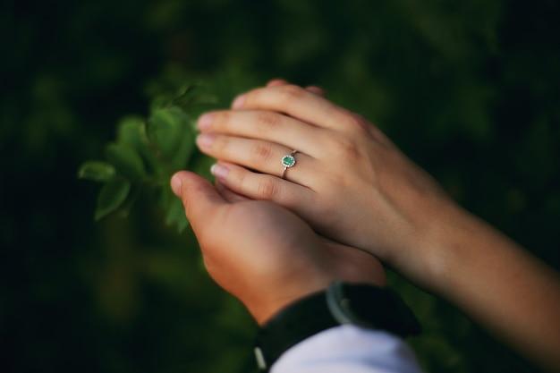 指輪を持つ若いカップルの手。