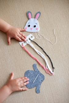 若い女の子の手のクローズアップ、彼女は糸からマクラメのおもちゃを縫います。