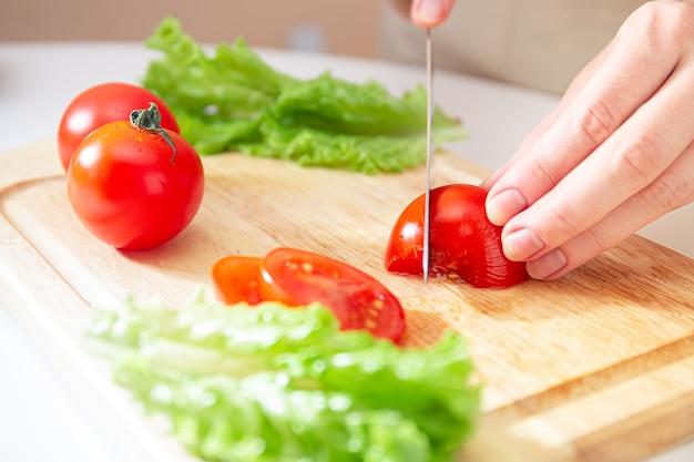 若い女の子の手は、木製のまな板の上でジューシーな赤いトマトを半分に切りました。材料と野菜の準備。ダイエット、栄養、健康的なライフスタイルのためのオーガニック製品。