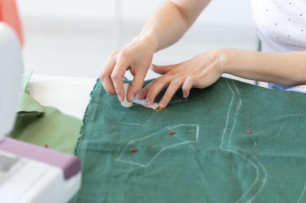 Руки молодой девушки-дизайнера делают отметки для нового шитья, сидя за столом рядом со швейной машиной. концепция творческого бизнеса и дизайна.