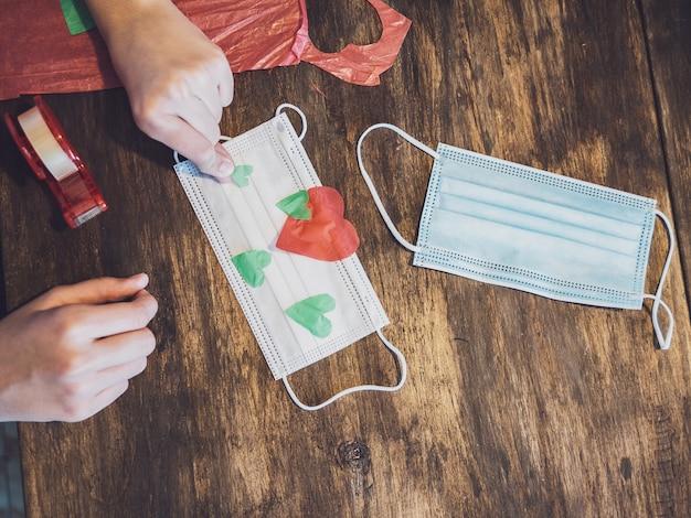 Руки молодой девушки делают поделки из бумаги и украшают хирургическую маску