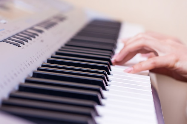 Руки молодой девушки рядом с клавишами пианино. девушка играет на пианино. исполнение музыкального произведения на фортепиано