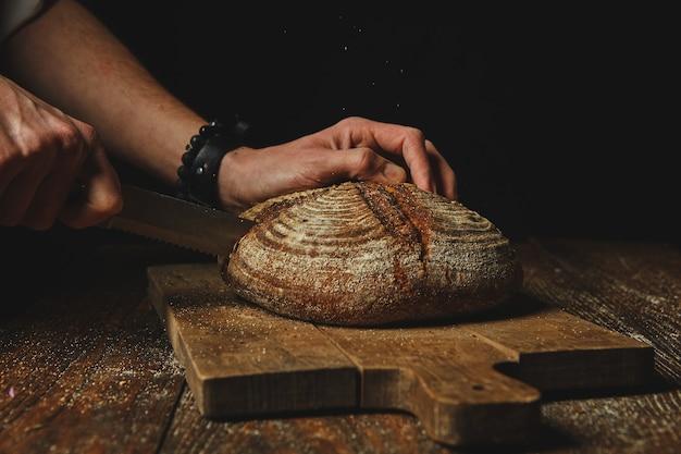 若い男の手が木製のまな板で焼きたてのライ麦パンを切る