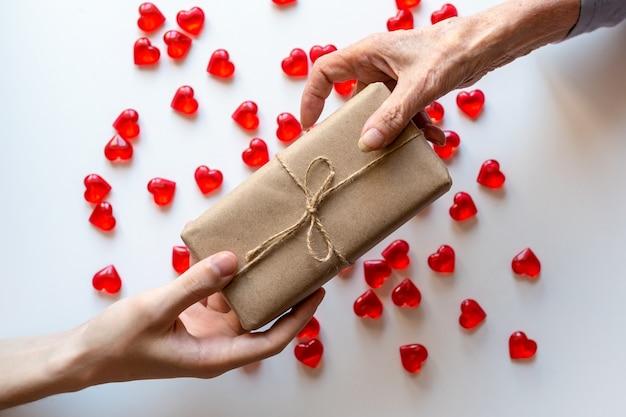 젊은 남자의 손에 노인 여성에게 선물을 제공합니다.