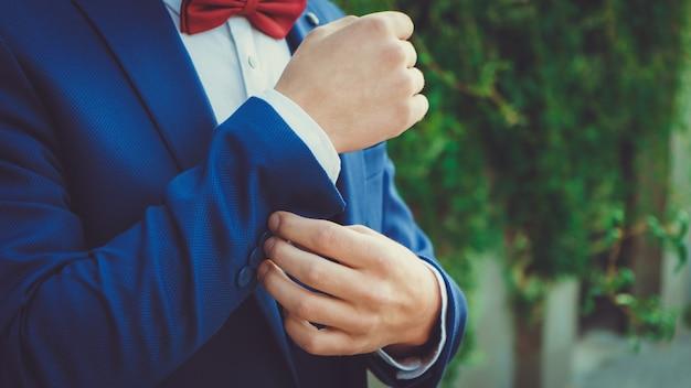 赤い蝶ネクタイと青いスーツを着た若い男の手がクローズアップ