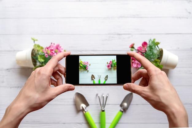 明るい木の表面に花のレイアウトの写真を撮る携帯電話を持つ若い男の手