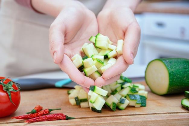 Руки молодой женщины нарезать ножом кубиками или ломтиками молодых огурцов кабачков на деревянной разделочной доске. подготовка ингредиентов и овощей перед приготовлением. здоровое питание.