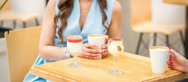 카페에서 테이블에 다른 칵테일과 함께 커피 한 잔을 들고 젊은 여자의 손