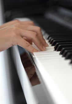 Hands of a young woman playing piano