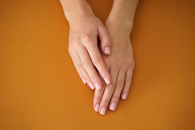 베이지 색 바탕에 아름 다운 매니큐어와 젊은 여자의 손. 여성 매니큐어. 확대.