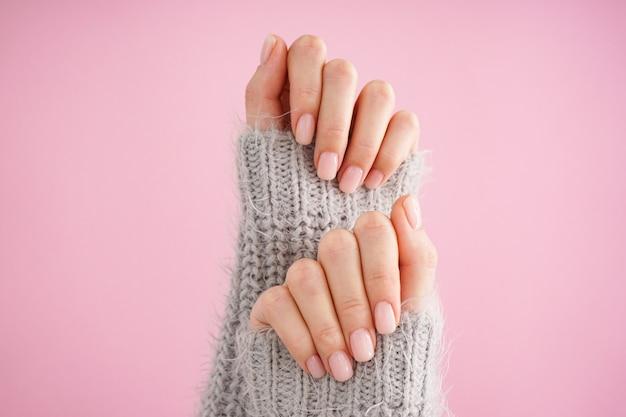 분홍색 바탕에 아름 다운 매니큐어와 젊은 여자의 손. 여성 매니큐어. 평평하다, 클로즈업.