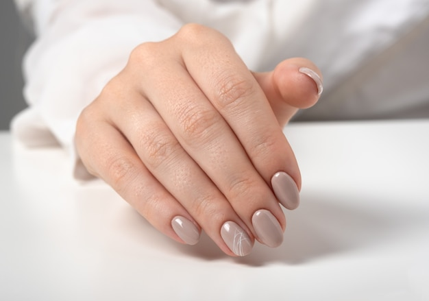 밝은 회색 배경에 베이지색 손톱을 가진 젊은 여성의 손. 매니큐어, 페디큐어 미용실 개념입니다. 텍스트 또는 로고를 위한 공간을 복사합니다. 젤 광택과 추상적인 흰색 거미줄 패턴입니다.