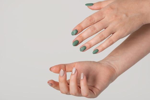 밝은 회색 배경에 녹색 올리브 무광택 손톱과 베이지색 광택 손톱을 가진 젊은 여성의 손. 다른 색상의 손톱입니다. 매니큐어, 미용실. 텍스트 또는 로고를 위한 공간을 복사합니다. 요약